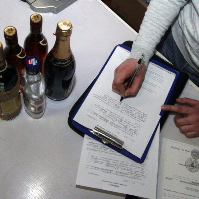 Таможенный сотрудник изымает алкоголь, который превышает норму ввоза
